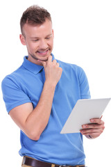 casual young man holds tablet and smiles