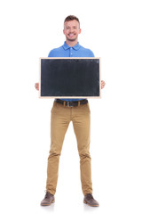 casual young man holds a small blackboard
