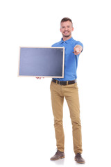 casual young man holds blackboard and points at you