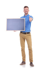 casual young man with blackboard shows thumbs up