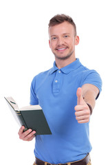 young casual man with book shows thumb up