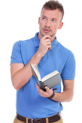 pensive young casual man holds book