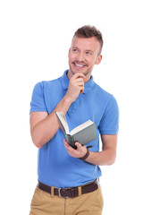 young casual man holds book and smiles pensively