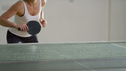Attractive woman playing table tennis indoors in slow motion