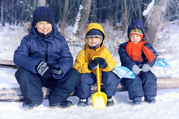 Three cheerful boy playing in a park in winter