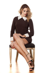 elegant young woman in a short dress sitting on a chair