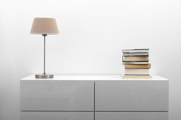white commode with lamp and books in bright minimalism interior