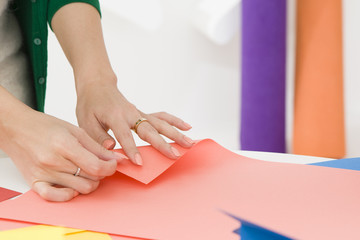 Woman folding colored paper