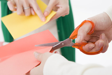 Women who cut the colored paper with scissors