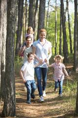 Familie geht mit Kindern im Wald spazieren