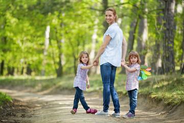 Mutter mit Zwillingen geht im Wald spazieren