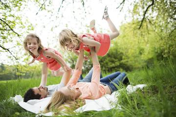 Familie mit indern macht Picknick im Grünen