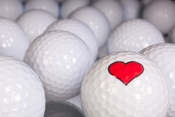 Golf balls with love symbol on the black glass table