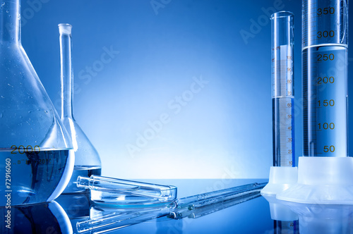Laboratory equipment, bottles, flasks on blue background