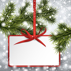 Paper gift card on spruce branches.