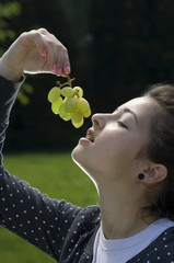 Girl with braces eating grapes