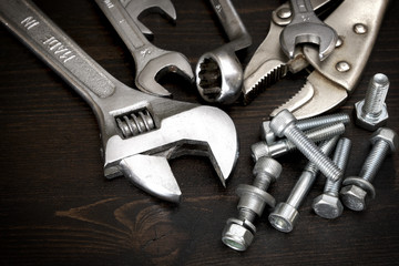 Nuts, bolts and tools on wooden surface