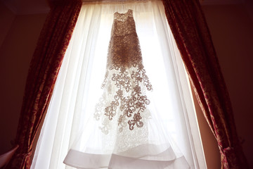White Wedding dress on a shoulders, before ceremony sunny window