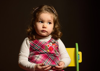 Close up portrait of a little girl with telephone in hands