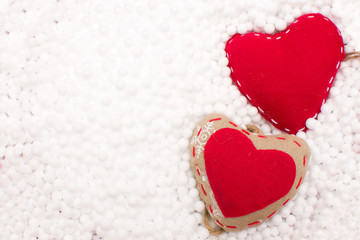 Two red hearts in snow