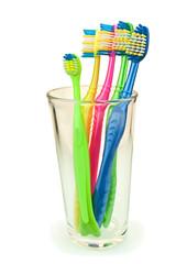 Зубные щетки в стакане изолированном белом фоне