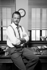 Smiling vintage businessman sitting on desk