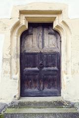 old wood door with metal knob in Prejmer fortified church, Braso