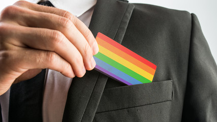 Man withdrawing a wooden card painted as the gay pride flag