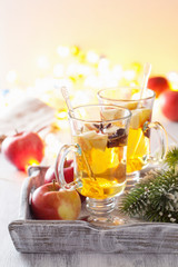 glass of mulled apple cider with orange and spices, christmas de