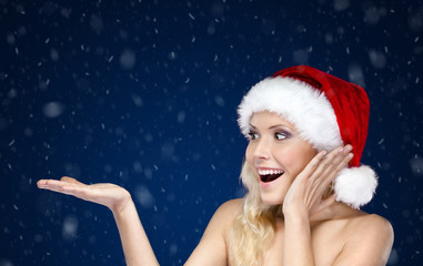 Pretty woman in Christmas cap gestures palm up