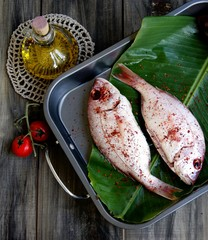 Fresh fish with vegetables on wooden boards