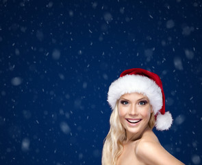 Beautiful woman in Christmas cap, snow background