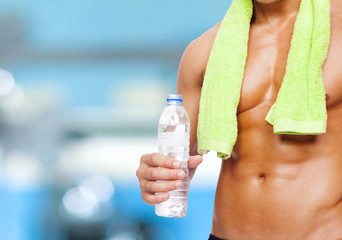 Fitness man holding a bottle of water at the gym