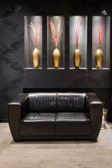 black leather couch in anteroom with golden flower vase