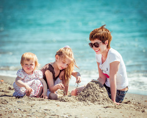 mother and daughters playing in the sand
