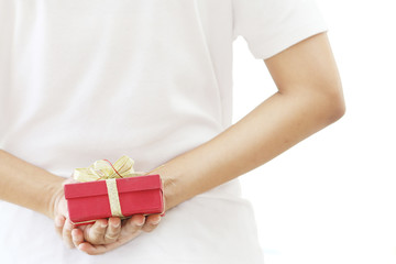 woman hiding red gift box behind her back