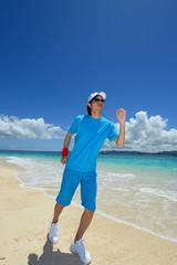 南国の海と走る男性