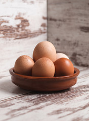 Eggs inside a clay plate over wooden background