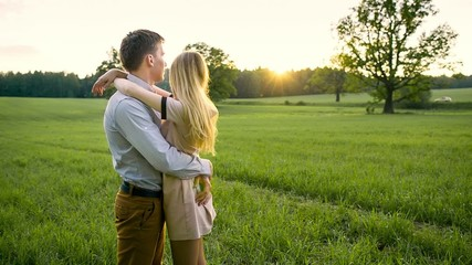 Young loving couple embracing in a field
