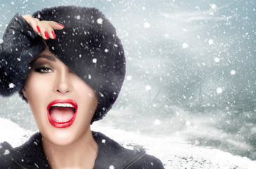 Winter Beauty. Fashion Model Girl in Fur Hat. Gestures and Grins