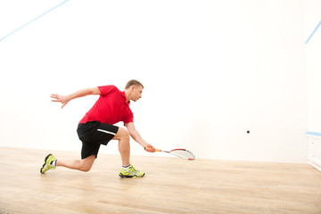 squash player hiting ball in squash court.