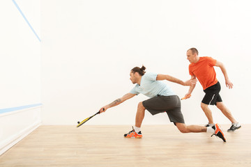 Two men playing match of squash.
