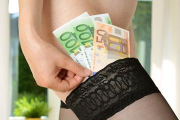 Frau steckt Geld in halterlosen Strumpf