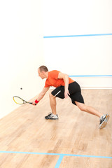 squash player hiting ball in squash court