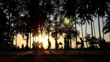 Men Silhouettes Playing Beach Football against Forest and Sunset