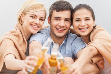 Man and two women relaxing on beach with beer.