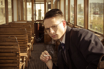 man with glasses in a suit sitting in an old wooden wagon train