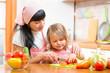 woman and kid girl preparing healthy food