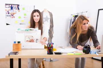 Young attractive females fashion designers leaning on office des