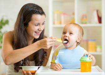 Mum spoon feeding child son